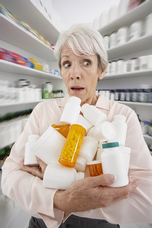 Woman in Pharmacy with Armful of Medicine