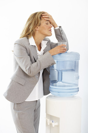Businesswoman Leaning on Water Cooler, Looking Ill