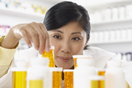 hair treatment: Portrait of Pharmacist Looking at Pill Bottles