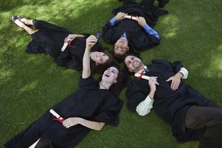 sms: College Graduates Lying on Ground Taking Pictures With Camera Phone LANG_EVOIMAGES