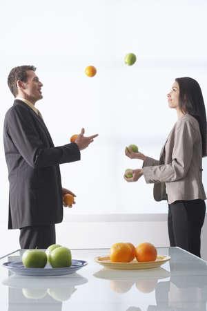 vómito: Gente de negocios malabares de manzanas y naranjas