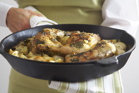 fryed: Close-up of Roasted Chicken Legs, Roasted Onions and Potatoes in Cast Iron Skillet LANG_EVOIMAGES