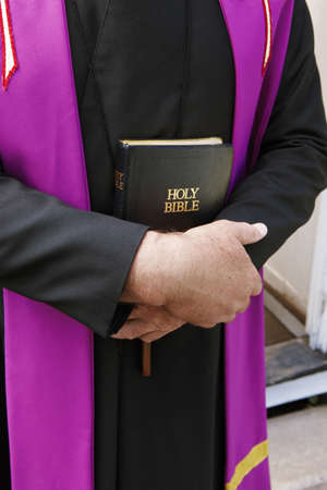Close-up of Priest Holding Bible