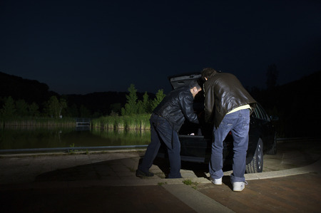Men Removing Something From Car Trunk at Night LANG_EVOIMAGES
