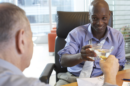 Businessmen Toasting in Office LANG_EVOIMAGES
