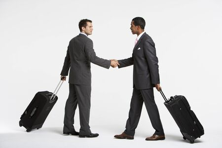 Businessmen With Luggage Shaking Hands LANG_EVOIMAGES