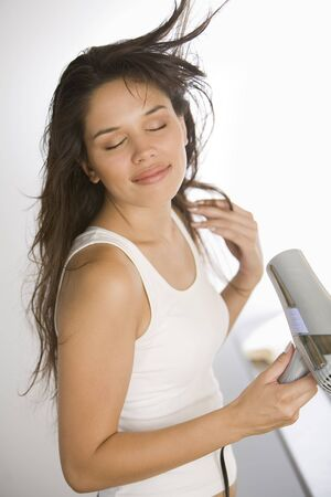 Woman Blow Drying Her Hair LANG_EVOIMAGES