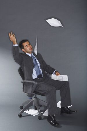 Frustrated Businessman Throwing Documents in Air LANG_EVOIMAGES