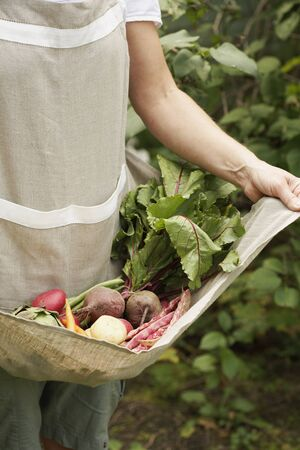 Woman Holding Apron of Vegetables LANG_EVOIMAGES