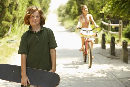 Boy Holding Skateboard and Girl Riding Bike on Country Road