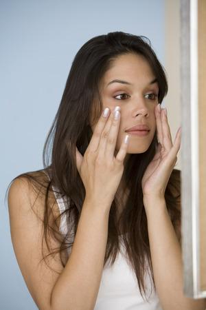 Mujer examinando su piel en el espejo