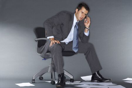 Angry Businessman Talking on Cell Phone Surrounded by Documents