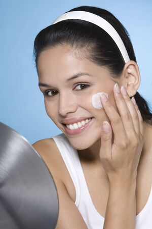 Portrait of Woman Applying Face Cream LANG_EVOIMAGES