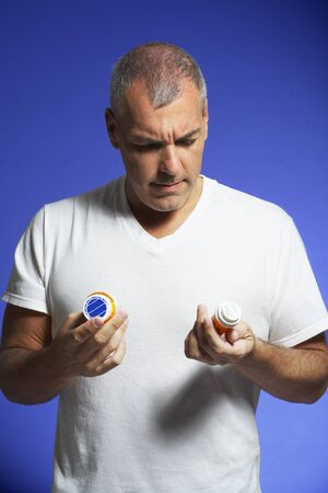 Man Looking at Pill Containers LANG_EVOIMAGES