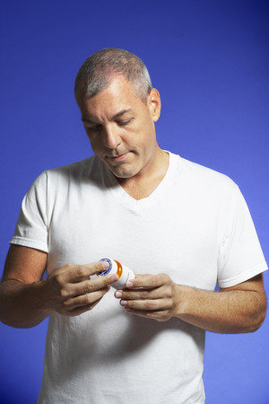 societal: Man Looking at Pill Container LANG_EVOIMAGES