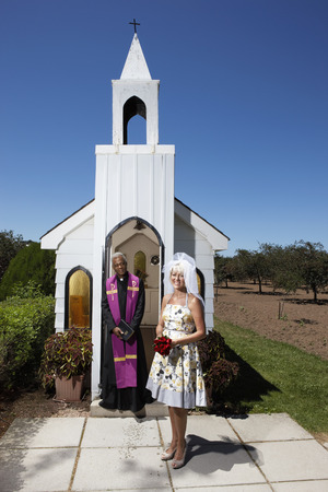 Bride and Priest Standing in Front of Church, Niagara Falls, Ontario, Canada LANG_EVOIMAGES