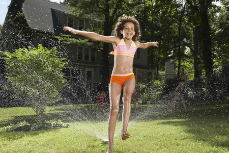 Family playing in backyard with sprinkler