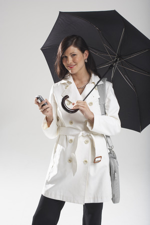 Portrait of Businesswoman Holding Umbrella and Sending Text Message