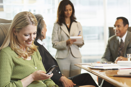 Businesswoman Using Her Cell Phone During Meeting LANG_EVOIMAGES