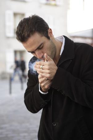 Man Lighting Cigarette, Paris, France LANG_EVOIMAGES