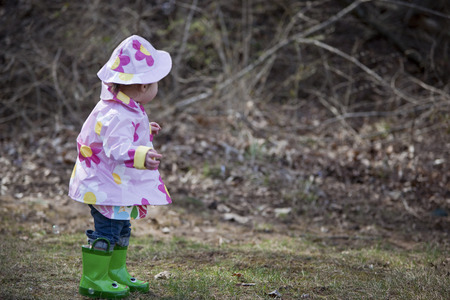 Little Girl in the Park Wearing Raincoat, Hat, and Boots, Bethesda, Maryland, USA
