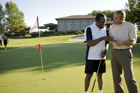 skepticism: Golfers Looking at Score Card, Burlington, Ontario, Canada LANG_EVOIMAGES