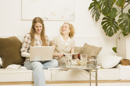 end of a long day: Two Women Sitting on Sofa Laughing