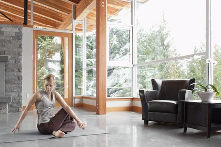 rafters: Woman Doing Yoga in Living Room of Large Alpine Home LANG_EVOIMAGES