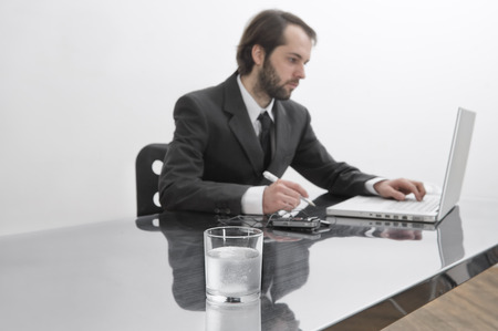 Tablets Dissolving in Glass of Water on Businessmans Desk