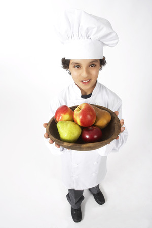 vocational high school: Boy Dressed Up as a Chef Holding Bowl of Fruit LANG_EVOIMAGES