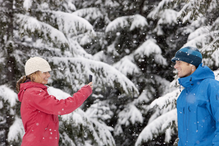 profile picture: Woman Taking Picture of Man with Camera Phone Outdoors in Winter, Whistler, British Columbia, Canada
