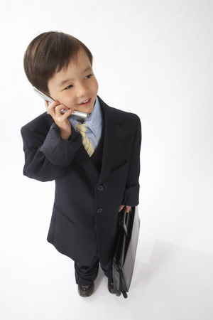 vocational high school: Little Boy Dressed Up as a Businessman Talking on Cell Phone LANG_EVOIMAGES