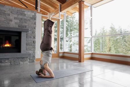 work life balance: Woman Doing Yoga in Living Room of Large Alpine Home LANG_EVOIMAGES