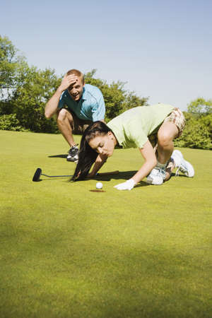 Golfer Trying to Blow Golf Ball Into Hole