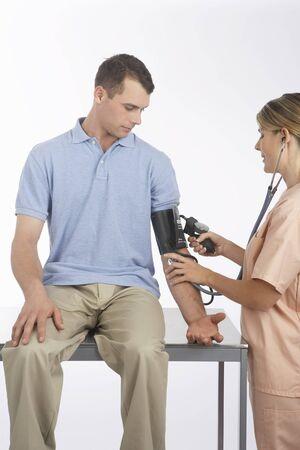 Nurse Testing Mans Blood Pressure LANG_EVOIMAGES