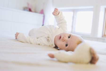 Baby Lying on Floor with Toy