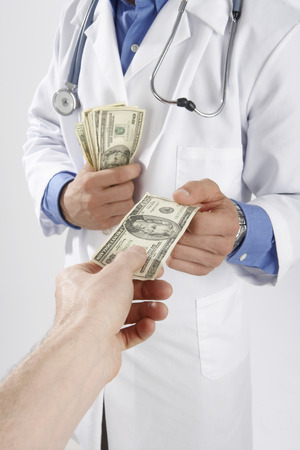 Man Giving Money to Doctor LANG_EVOIMAGES