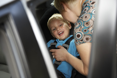 Mother Putting Son in Car Seat LANG_EVOIMAGES