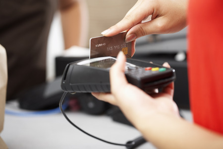 electronic commerce: Woman using Card Reader at Checkout Counter LANG_EVOIMAGES