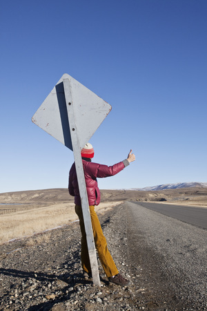 Woman Hitchhiking on a Remote Road, Patagonia, Argentina LANG_EVOIMAGES