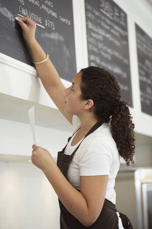 Girl Writing on Menu Board at Cafe LANG_EVOIMAGES