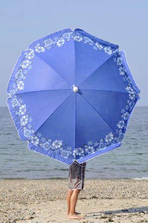 Muchacho con el paraguas en la playa LANG_EVOIMAGES