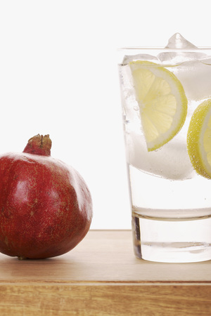 seltzer: Still Life of Pomegranate and Glass of Sparkling Water with Lemon Slices