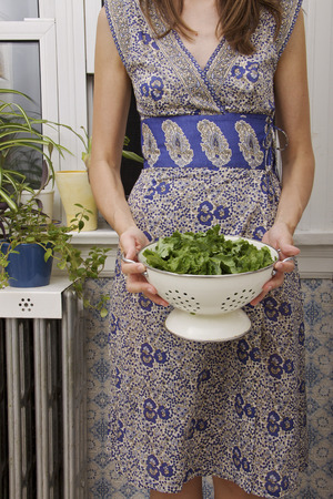 Woman Holding a Colander of Organic Rapini