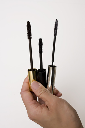 comparable: Close-up of Womans Hand Holding Mascara Applicators LANG_EVOIMAGES