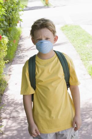 ah1n1: Little Boy Walking to School Wearing a Face Mask