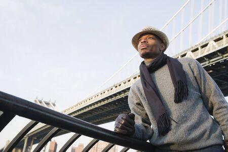Man Standing in front of Bridge LANG_EVOIMAGES
