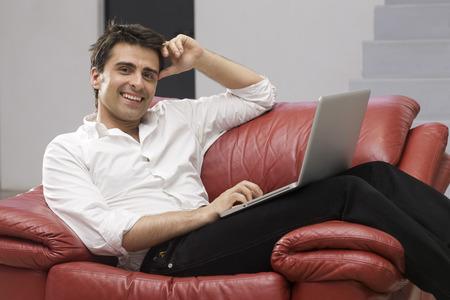 homeoffice: Businessman Sitting on Sofa Using Laptop Computer LANG_EVOIMAGES