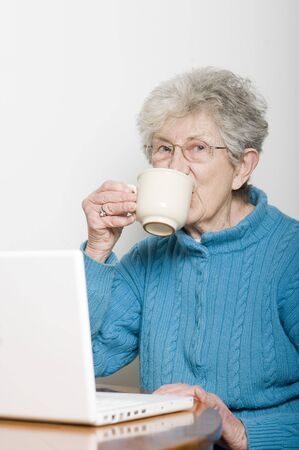 Senior Woman Using Laptop Computer and Drinking a Cup of Coffee