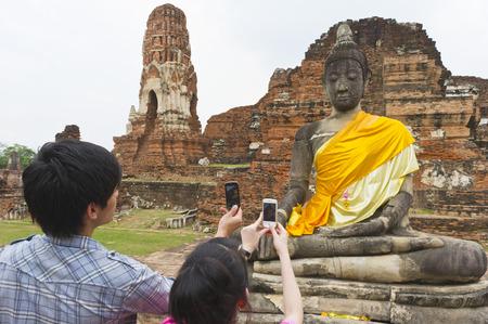 phra nakhon si ayutthaya: Couple Taking Photos of Buddha Statue, Wat Mahathat, Ayutthaya, Ayutthaya Province, Thailand LANG_EVOIMAGES